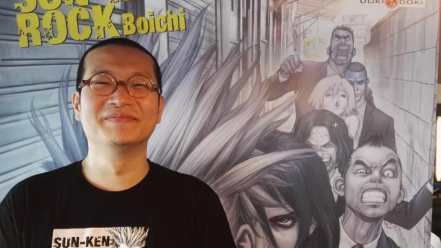 Boichi na frente de um cartaz de Sun Ken Rock