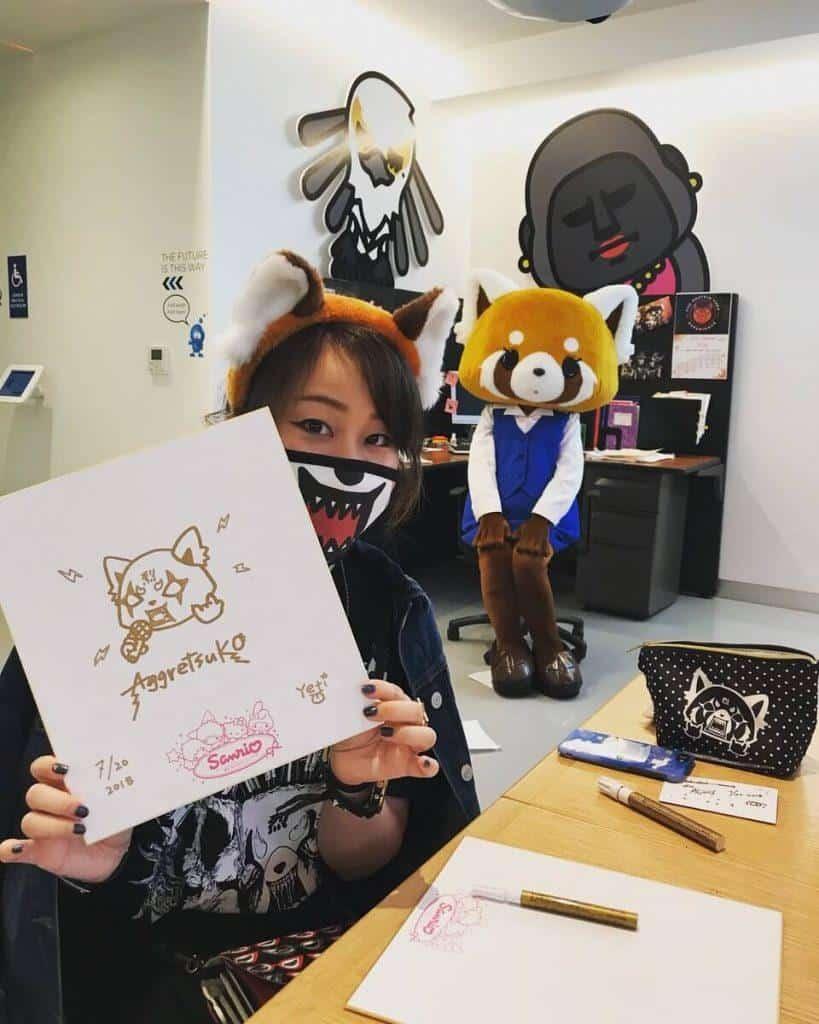 A criadora de Resuko, Yeti, segurando uma folha escrito Aggretsuko