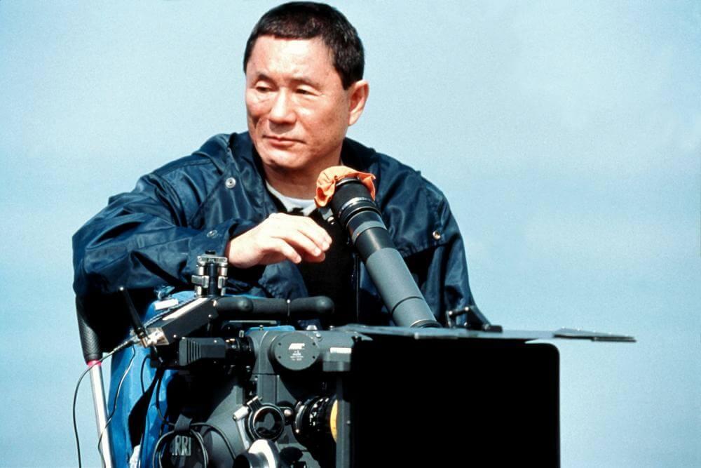 Diretor japones sentado em uma grua atrás de uma camera