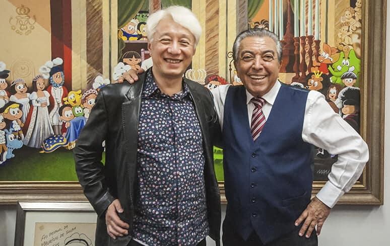 Mauricio de Souza e Osuma Tezuka na história dos animes abraçados e sorrindo, como amigos