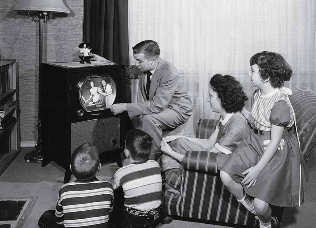 Familia sentada na frente de uma televisão nos anos 50