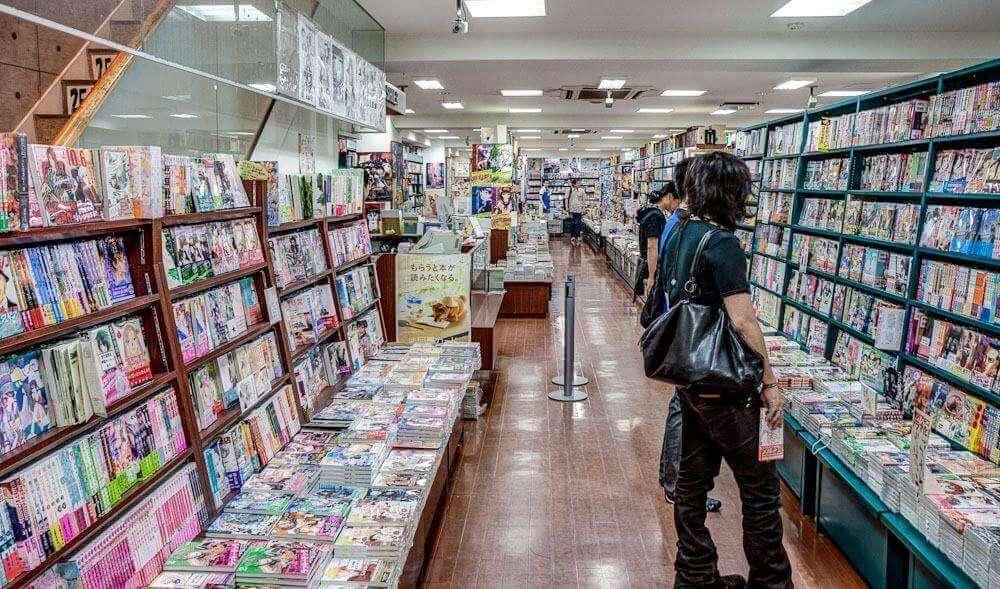 loja de mangás no japão com três pessoas olhando as prateleiras cheias de mangás