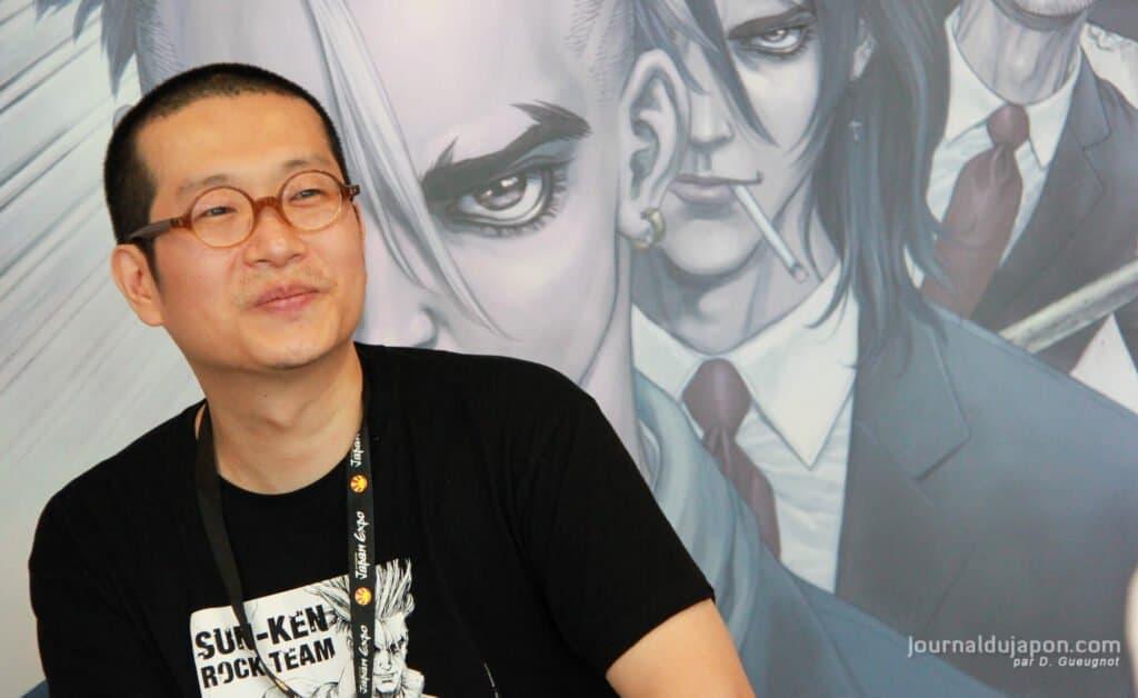 Boichi na frente de um painel com personagens de Sun-Ken Rock