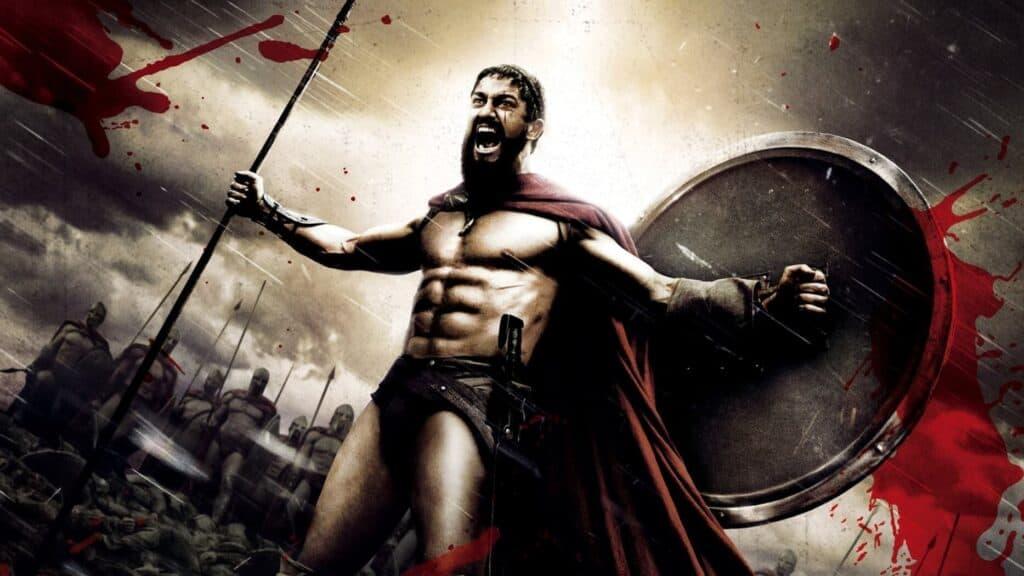 Rei Leonidas segurando uma lança e um esudo e desafiando um exército