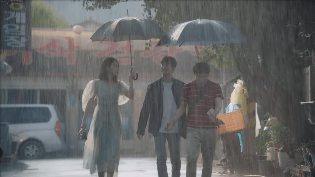 Imagem da série Its Okay To Not Be Okay com Ko Mun-yeong, Moon Gang-tae e Moon Sang-tae na chuva