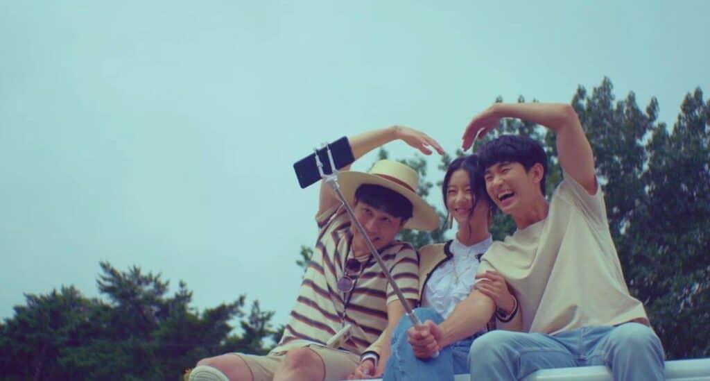 Imagem retirada da série Its Okay To Not Be Okay da Ko Mun-yeong e os irmãos Moon sentados um ao lado do outro sorrindo e tirando foto