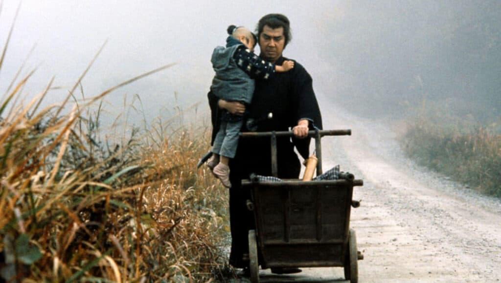 Cena do filme lobo solitário no qual o protagonista leva seu filho no colo e com a outra mão empurra o carrinho de bebe