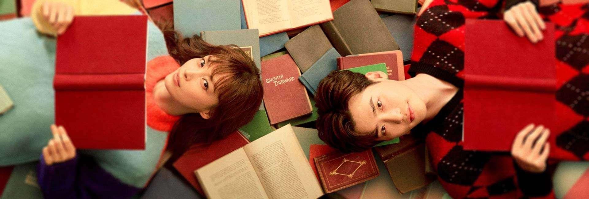 Na imagem mostramos uma das recomendações da lista, o dorama love is a bonus book, com os dois protagonistas deitados em cima de vários livros enquanto seguram com as duas mãos 1 livro cada um deles
